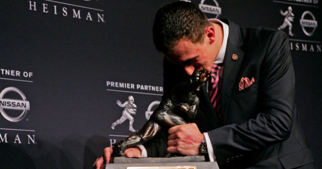 Dec 8, 2012; New York, NY, USA; Texas A&M Aggies quarterback Johnny Manziel kisses the 2012 Heisman Trophy after a press conference at the Marriott Marquis in downtown New York City.  Mandatory Credit: Jerry Lai-USA TODAY Sports ORG XMIT: USATSI-118758 ORIG FILE ID:  20121208_jel_sl8_210.jpg