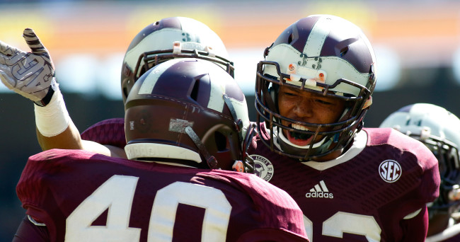 Nov 1, 2014; College Station, TX, USA; Texas A&M Aggies linebacker Shaan Washington (33) celebrates a tackle with lineman Jarrett Johnson (40) against Louisiana Monroe Warhawks during the second quarter at Kyle Field. Texas A&M Aggies won 21-16. Mandatory Credit: Ray Carlin-USA TODAY Sports