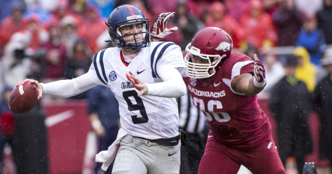 Nov 22, 2014; Fayetteville, AR, USA; Ole Miss Rebels quarterback Ryan Buchanan (9) looks to pass under pressure from Arkansas Razorbacks defensive end Trey Flowers (86) during first half action at Donald W. Reynolds Razorback Stadium. Mandatory Credit: Beth Hall-USA TODAY Sports