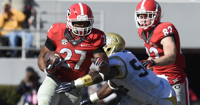 Nov 29, 2014; Athens, GA, USA; Georgia Bulldogs running back Nick Chubb (27) runs past Georgia Tech Yellow Jackets linebacker Quayshawn Nealy (54) during the first half at Sanford Stadium. Mandatory Credit: Dale Zanine-USA TODAY Sports