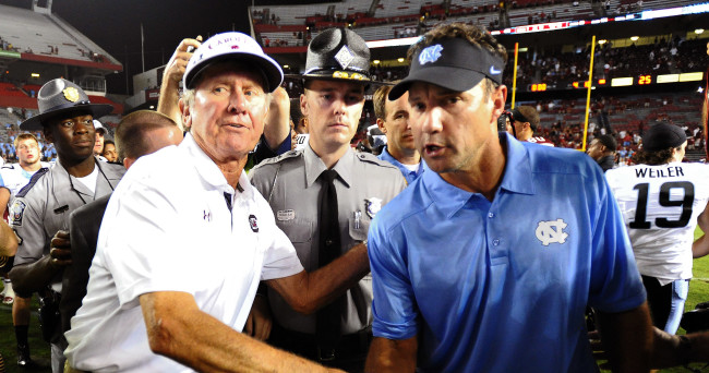 South Carolina head coach Steve Spurrier, left, shakes hands with North Carolina head coach Larry Fedora, right, at the end of an NCAA college football game, Thursday, Aug. 29, 2013, in Columbia, S.C. A severe weather delay was called in the fourth quarter due to lighting in the area. South Carolina defeated North Carolina 27-10. (AP Photo/Stephen Morton)