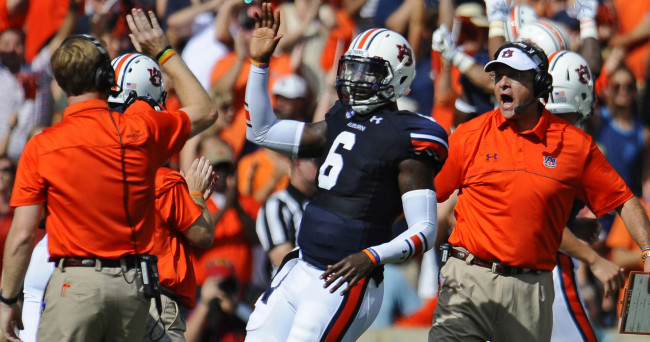 Aug 30, 2014; Auburn, AL, USA; Auburn Tigers offensive coordinator Rhett Lashlee (left) high-fives quarterback Jeremy Johnson (6) after a touchdown  as head coach Gus Malzahn celebrates in the background against the Arkansas Razorbacks at Jordan Hare Stadium. Mandatory Credit: Shanna Lockwood-USA TODAY Sports