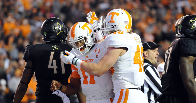 Nov 29, 2014; Nashville, TN, USA; Tennessee Volunteers quarterback Josh Dobbs (11) celebrates after a touchdown run during the first half against the Vanderbilt Commodores at Vanderbilt Stadium. Mandatory Credit: Christopher Hanewinckel-USA TODAY Sports