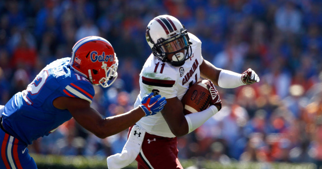 Nov 15, 2014; Gainesville, FL, USA; South Carolina Gamecocks wide receiver Pharoh Cooper (11) runs with the ball as Florida Gators defensive back Quincy Wilson (12) defends during the first quarter at Ben Hill Griffin Stadium. Mandatory Credit: Kim Klement-USA TODAY Sports