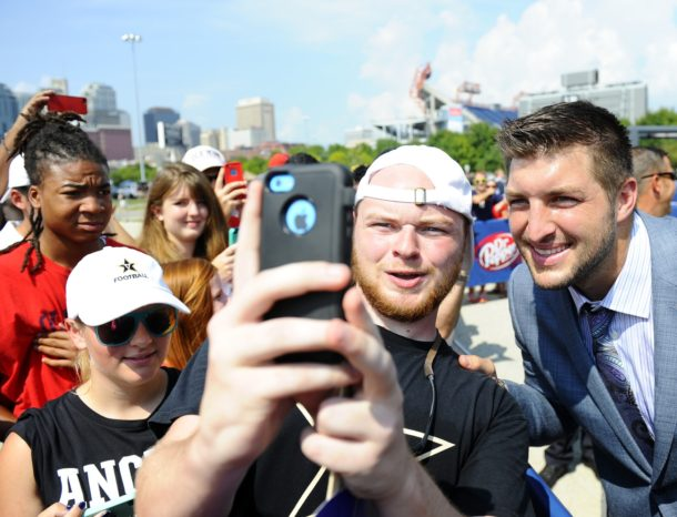 Sep 6, 2014; Nashville, TN, USA; SEC Network host Tim Tebow poses for pictures with fans gathered to watch the SEC Nation show prior to the Vanderbilt Commodores game against the Mississippi Rebels at LP Field. Mandatory Credit: Christopher Hanewinckel-USA TODAY Sports