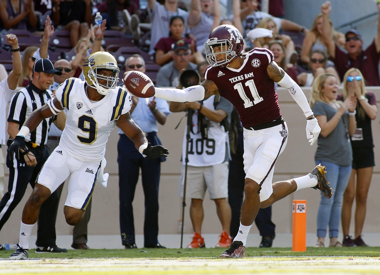Sep 3, 2016; College Station, TX, USA; Texas A&M Aggies wide receiver Josh Reynolds (11) goes in the for a 40-yard touchdown catch against UCLA Bruins defensive back Marcus Rios (9) during the second half at Kyle Field. Texas A&M won in overtime 31-24. Mandatory Credit: Ray Carlin-USA TODAY Sports