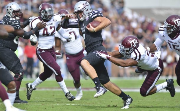 Nov 5, 2016; Starkville, MS, USA; Mississippi State Bulldogs quarterback Nick Fitzgerald (7) carries the ball as defended by Texas A&M Aggies linebacker Shaan Washington (33) during the first quarter of the game at Davis Wade Stadium. Mandatory Credit: Matt Bush-USA TODAY Sports