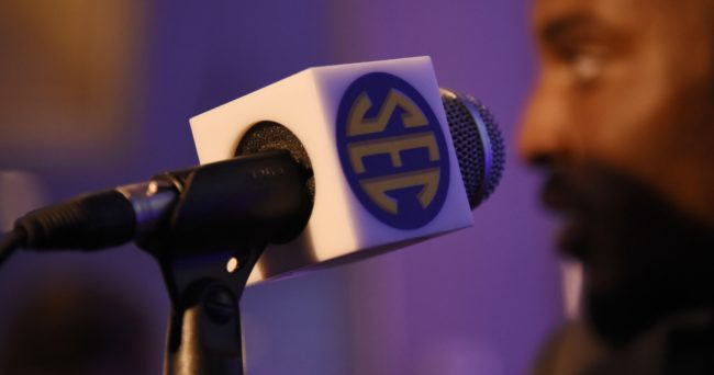 Jul 15, 2015; Birmingham, AL, USA; General view of a microphone with an SEC logo while Kentucky Wildcats safety A.J. Stamps (background) speaks to media during SEC media day at the Wynfrey Hotel. Mandatory Credit: Shanna Lockwood-USA TODAY Sports