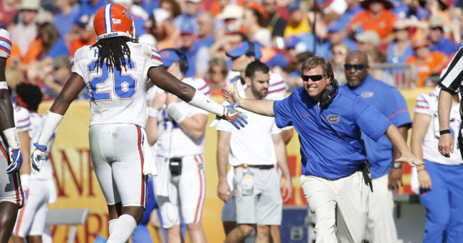 Jan 2, 2017; Tampa , FL, USA; Florida Gators head coach Jim McElwain (R) high fives defensive back Marcell Harris (26) against the Iowa Hawkeyes during the first half at Raymond James Stadium. Mandatory Credit: Kim Klement-USA TODAY Sports