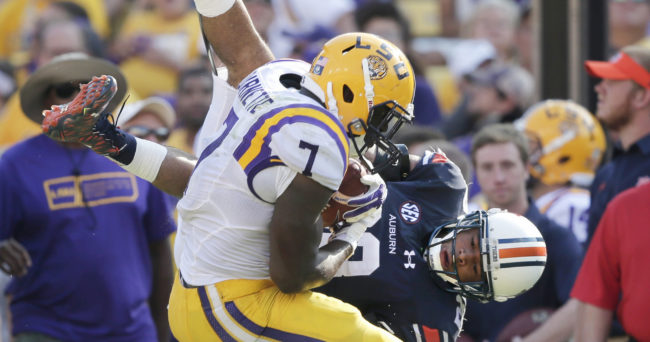 Sep 19, 2015; Baton Rouge, LA, USA;  Auburn Tigers defensive back Trey Matthews (28) jumps over Louisiana State Tigers running back Leonard Fournette (7) to try to get the ball loose in the second half at Tiger Stadium. Fournette kept running to score his second touchdown of the game. Mandatory Credit: Erich Schlegel-USA TODAY Sports